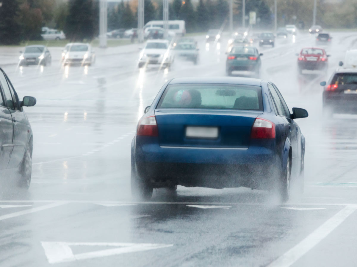 Blue car driving on a rainy road in traffic